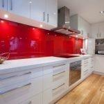 Белая мебель и красный фартук в интерьере кухни