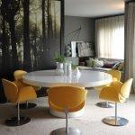 Желтые кресла на ножках вокруг белого стола