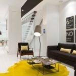 Желтый ковер и черная мебель