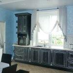 Сочетание голубых стен и черной мебели на кухне