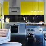 Сочетание черного фартука и желтой мебели