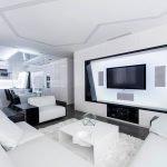 Белый угловой диван и столик напротив телевизора